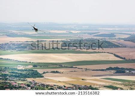 Small plane flies over the large country. View from above. - stock photo