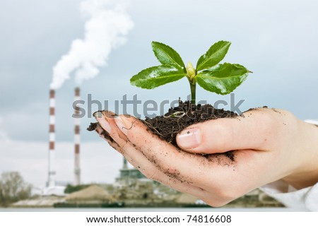 Small plant growing in the human hands and pollution smoke from factory chimneys in background. - stock photo