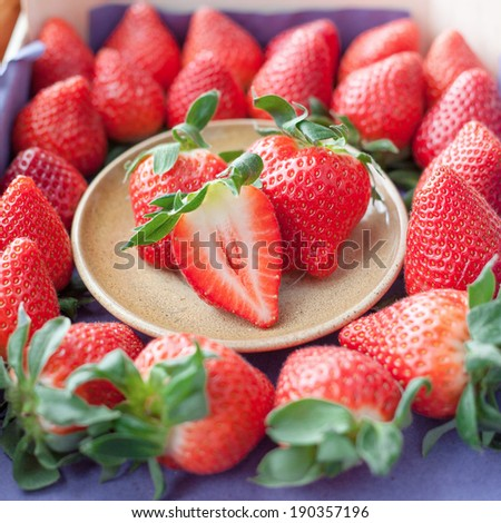 Small plate filled with succulent juicy fresh ripe red strawberries in a box of strawberries - stock photo