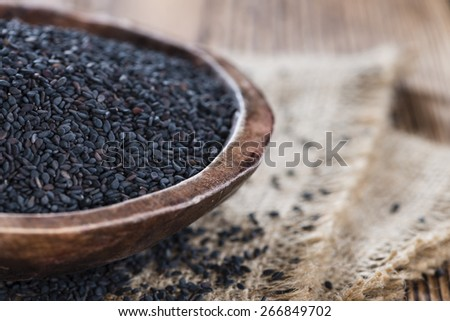 Small portion of black Sesame (close-up shot) on wooden background - stock photo