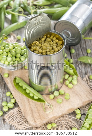 Small portion of canned Peas with some fresh pods - stock photo
