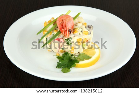 Small portion of food on big plate on wooden table - stock photo
