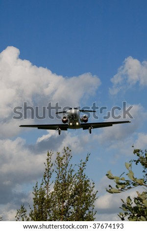 small private business jet on runway landing approach - stock photo