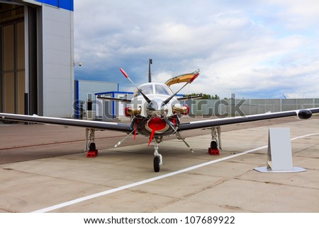 small private propeller aircraft with one engine on the background of a hangar in cloudy weather - stock photo