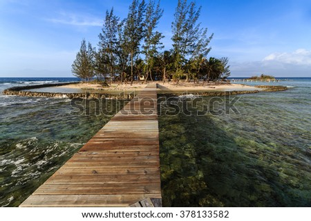 Small private tropical island and dock in Caribbean - stock photo