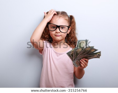 Small professor in eye glasses scratching head, holding money and thinking how earring more. Kid have a big idea. Emotional portrait on blue background with empty copy space - stock photo