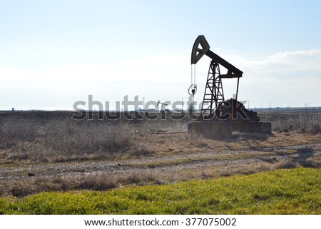 Small Pumpjack in a field - stock photo