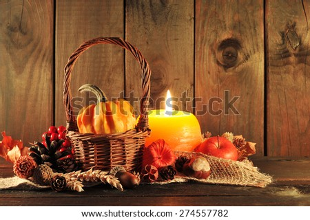 small pumpkin in basket on old weathered wooden floor in candlelight - stock photo