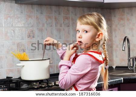 small puzzled girl cooking - stock photo