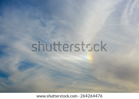Small rainbow in a clouds on blue sky - stock photo