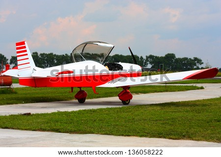 small red airplane under sky in field taken in summer in Ukraine - stock photo