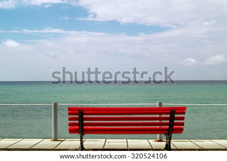 Small red bench overlooking the Aegean sea - stock photo