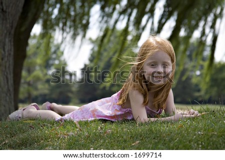 Small red-haired girl laying in the grass under willow trees.