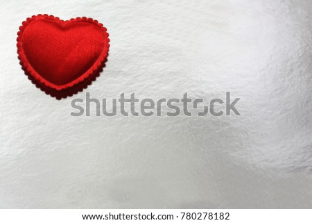 small red heart made of fabric on a silver background