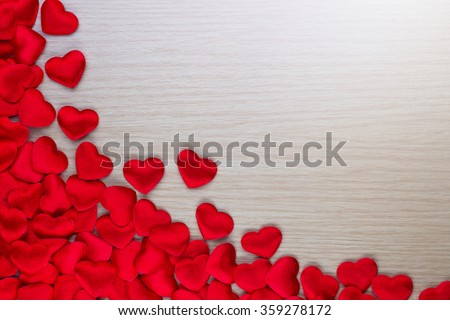 Small red hearts gather on left side of wood table with space for text on right side, perfect for Valentine's day card background