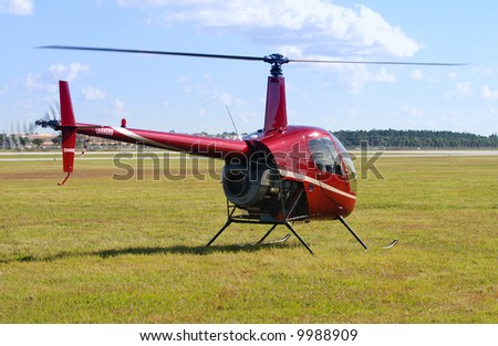 Small red helicopter on the ground - stock photo