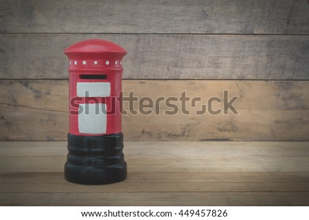 Small red post box on wood background - stock photo