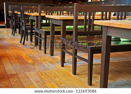 Small restaurant interiour with wooden floor and furniture - stock photo