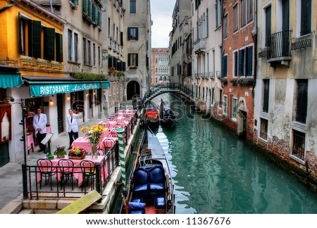 Small restaurant on venetian canal among old houses in Venice, Italy. - stock photo