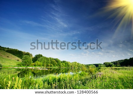 Small river and sun in the blue sky. - stock photo