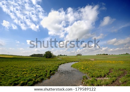Small river, framland and blue and cloudy sky. - stock photo