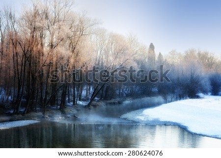 Small river in winter, with sunbeams filtering through bare birch trees. Winter landscape. Winter wonderland. Winter background. - stock photo