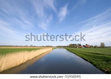 Small river through a farmland in Holland during Spring - stock photo