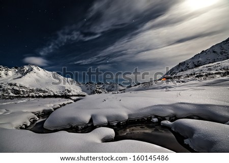 Small river through snowdrift. Night shoot with moonlight - stock photo