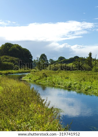 small river winding through natural countryside landscape - stock photo