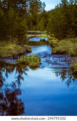 Small river with motion blured water,flowing through green forest at mountain / Mountain river - stock photo