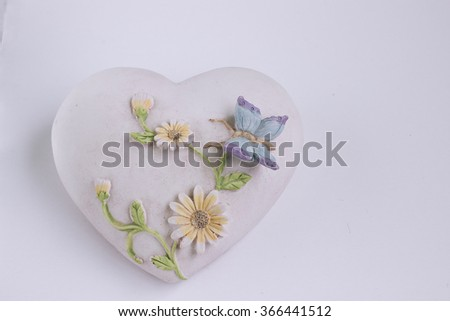 small rock in heart shape with flowers an butterfly - stock photo