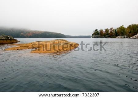 Small rock island in Killarney lake at overcast day - stock photo