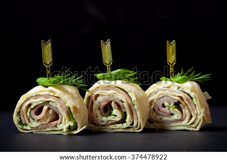 Small rolls with ham, cheese and pita on skewer on a black slate plate. Selective focus. Toned. - stock photo