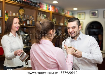 Small romantic  bar with female barista and two clients at counter - stock photo