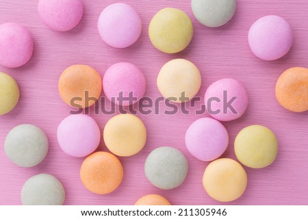 Small round candy-colored pastels on pastel background.  - stock photo