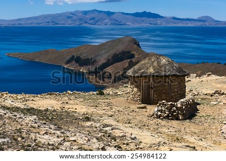 Small round stone hut with thatched roof on Isla del Sol (Island of the Sun) in Lake Titicaca, Bolivia. The island is a popular tourist destination.  - stock photo