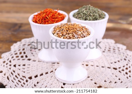 Small round tea bowls with different seasoning on a white lace napkin on a tray on wooden background
