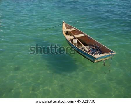 small row boat floating on clear water - stock photo