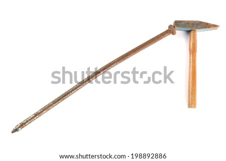 Small rusty hammer and big rusty nail - stock photo