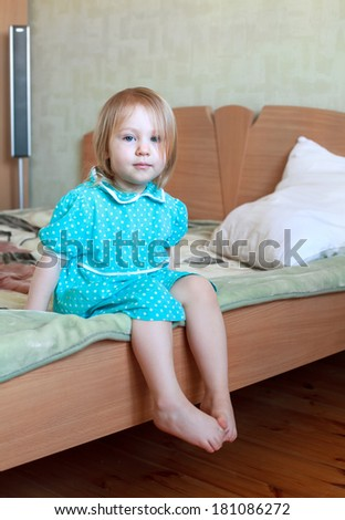 Small sad blonde girl in blue dress sitting on the bed dangling her legs, selective focus on face  - stock photo
