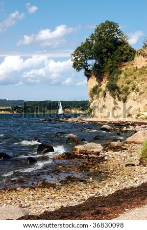 Small sailboat in front of the cliffs on the Rügen island - stock photo