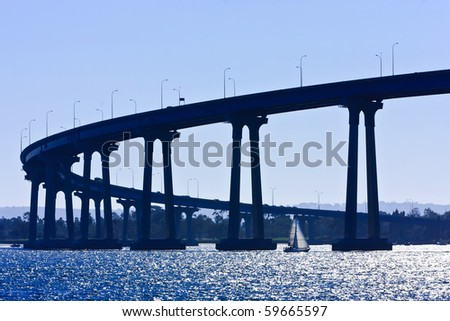 Small sailboat under the San Diego - Coronado Bridge, locally referred to as the Coronado Bridge, crossing over San Diego Bay in the United States, linking San Diego, with Coronado, California. - stock photo