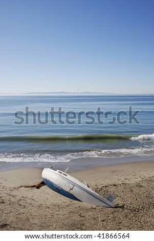 Small sailboat washed up on shore. - stock photo