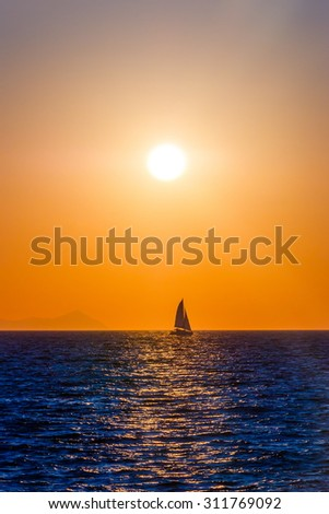 Small sailing boat on the sea in red sunset
