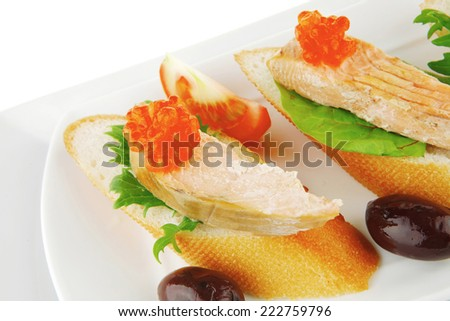 small salmon sandwiches served with caviar and olives - stock photo
