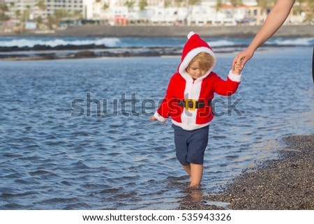 small santa claus cute boy or child barefoot in red new year coat with white fur and hat celebrates christmas or xmas holidays at sand beach near sea or ocean water sunny outdoor on natural background