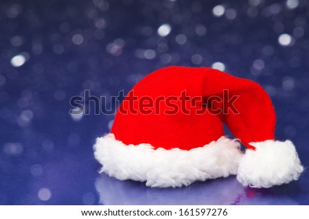 Small Santa hat on white sparkle background. Santa hat on snowing night background.  - stock photo