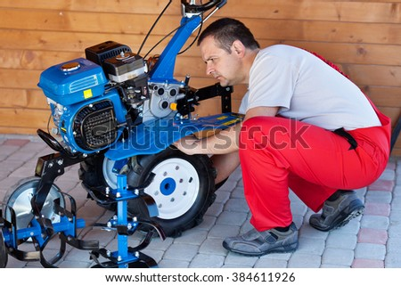 Small scale agriculture and sustainability - man checking on small motorized tiller machine - stock photo