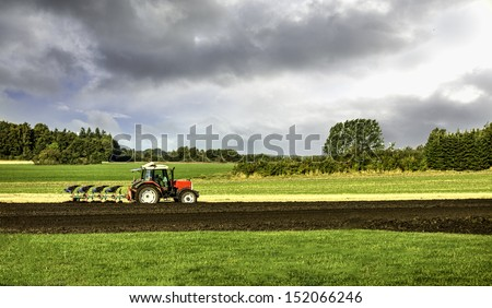 Small scale farming with tractor and plow in field - stock photo