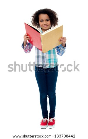 Small school girl reading a book isolated on white background. - stock photo